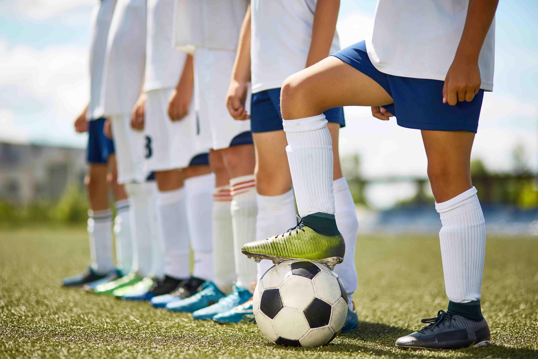 młodzi piłkarze czekający na rozpoczęcie meczy, na łydkach mają ochraniacze piłkarskie