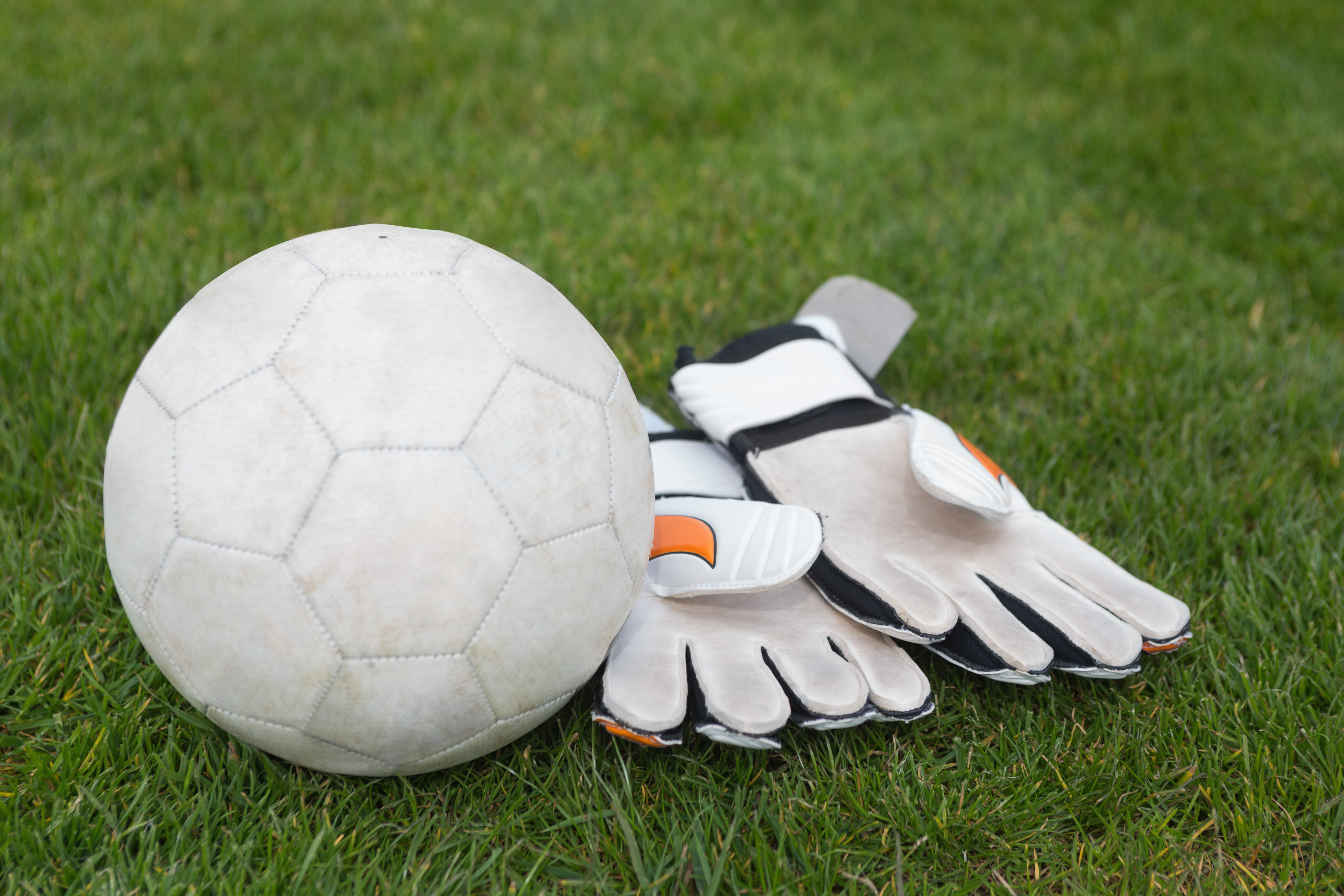 Goalkeeping gloves and football on pitch on a clear day