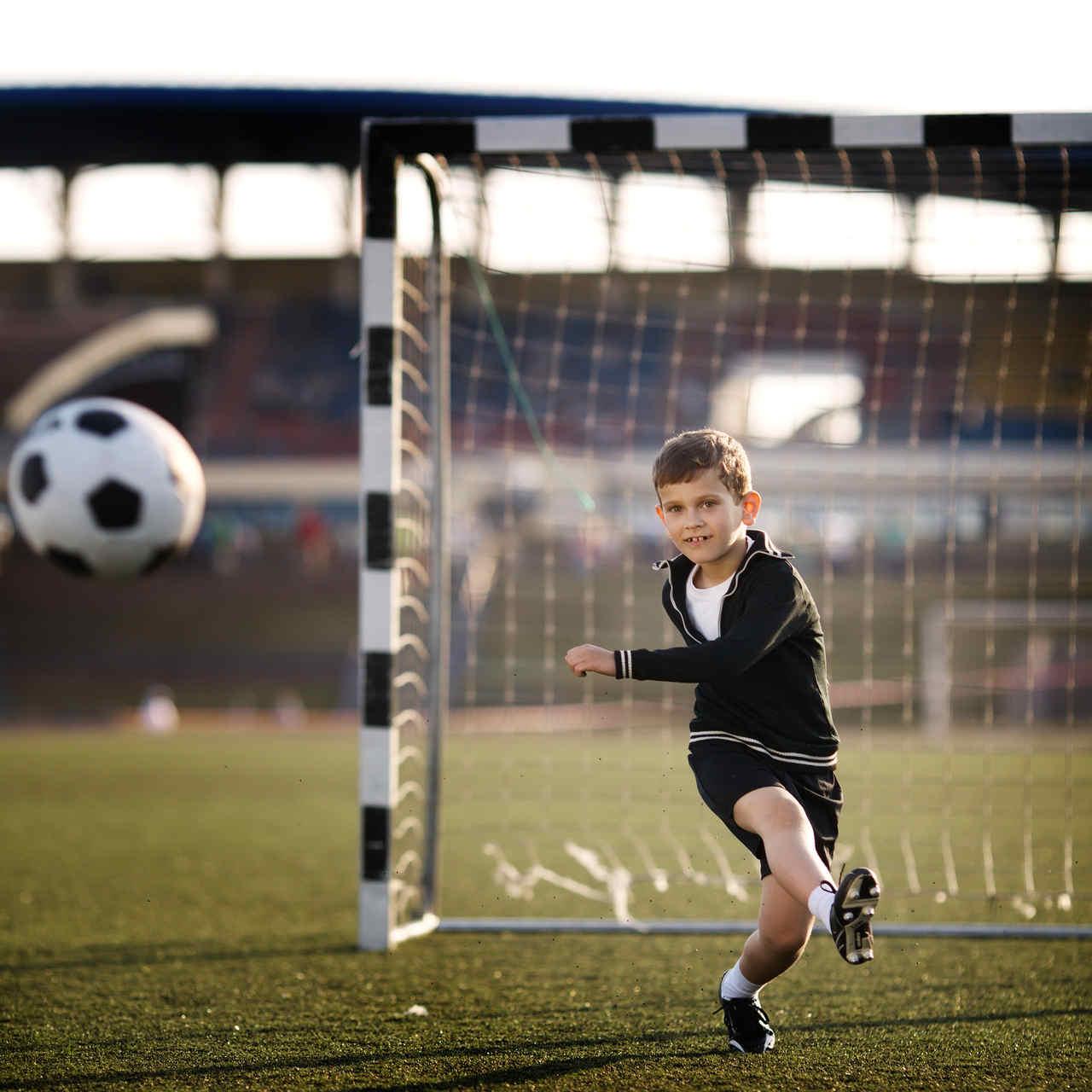 chłopiec trenujący piłkę nożną w chłodne dni